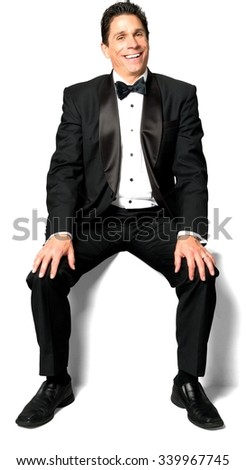 Friendly Caucasian man with short black hair in a tuxedo sitting with hands holding knee - Isolated - stock photo