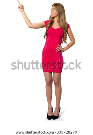 Friendly Caucasian young woman with long light blond hair in evening outfit with hands on hips - Isolated