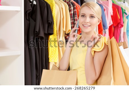 Friendly chat. Close-up of a smiling blond girl talking over the phone and holding paper bags copyspace  - stock photo