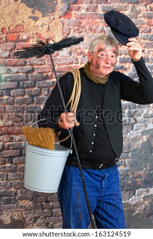 Friendly chimney sweep saying hello with his cap - stock photo