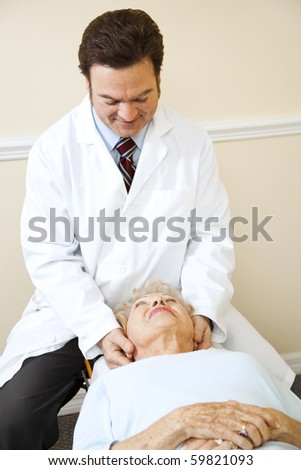 Friendly chiropractor adjusts a senior woman's cervical spine (neck). - stock photo