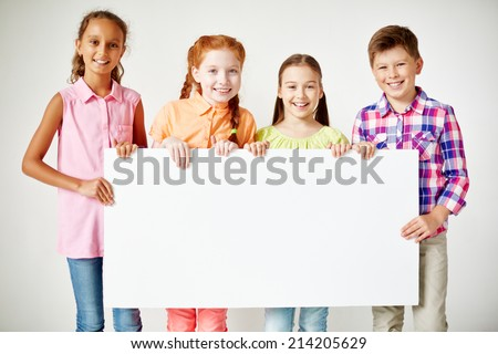 Friendly classmates with blank paper looking at camera with smiles - stock photo