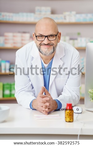 Friendly confident male pharmacist wearing glasses leaning on the counter in the pharmacy smiling at the camera