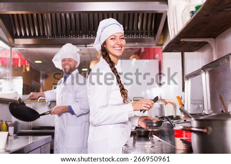 Friendly cooks greeting customers at bistro kitchen  - stock photo