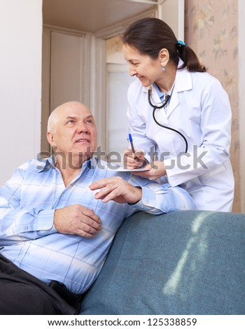 Friendly doctor asked male mature patient feels at hospital - stock photo