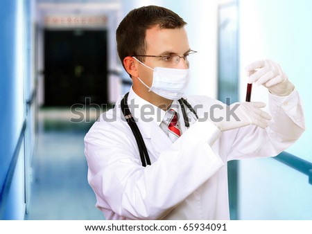 Friendly doctor -intern resarch a medical test glass with blood . - stock photo
