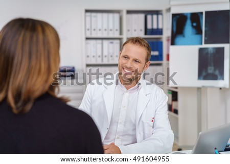 Friendly doctor or consultant interviewing a female patient in his surgery or at the hospital with over the shoulder focus to his smiling face