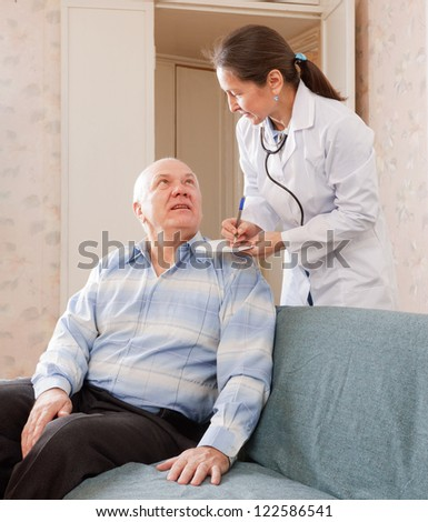 friendly doctor talks with  senior male patient - stock photo