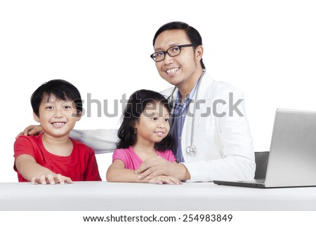 Friendly doctor with children smiling at camera, isolated on white background - stock photo