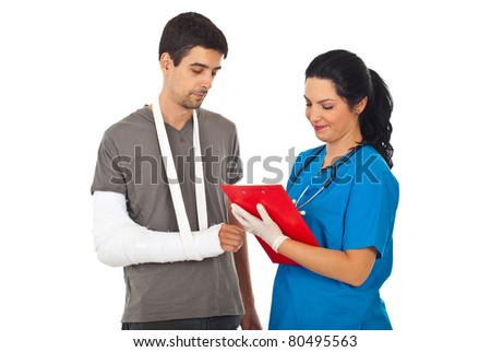 Friendly doctor woman giving prescription to injured man and writing in clipboard isolated on white background - stock photo