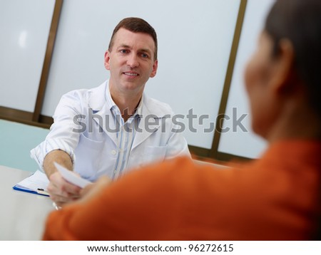 Friendly doctor working and giving assistance to female mature patient in hospital office, writing prescription medicine - stock photo