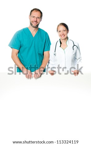 friendly doctors holding  a white blank board - stock photo