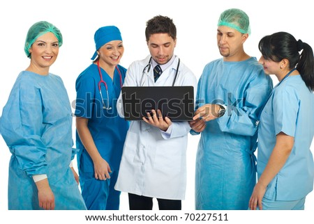 Friendly doctors using a laptop and a smiling surgeon woman looking at camera isolated on white background