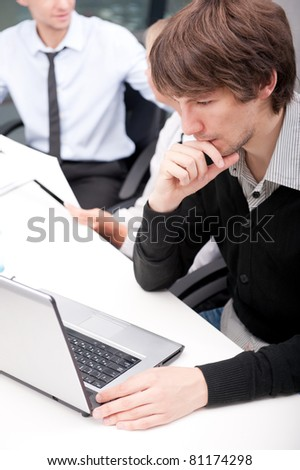 Friendly executive sitting in front of laptop at his workplace. He is looking at the screen of his computer very attentive. His colleagues at the background