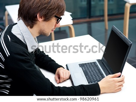 Friendly executive sitting in front of laptop in his office. - stock photo
