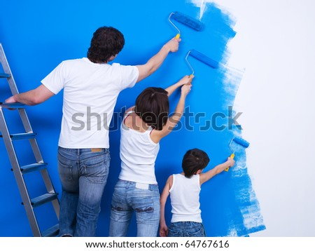 Friendly family brushing the wall together into the blue color - stock photo