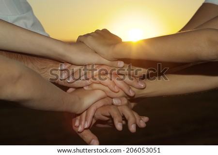 Friendly family hands closeup against the sunset  - stock photo
