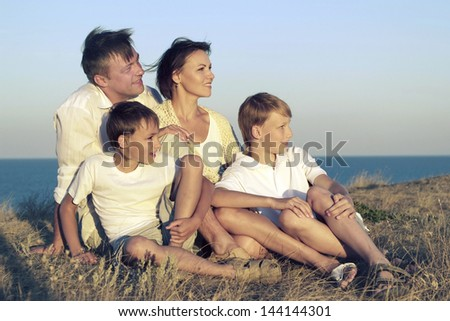 friendly family of four in white on a background of a sunset