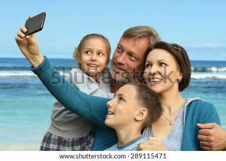 friendly family of four on a background of a seashore - stock photo