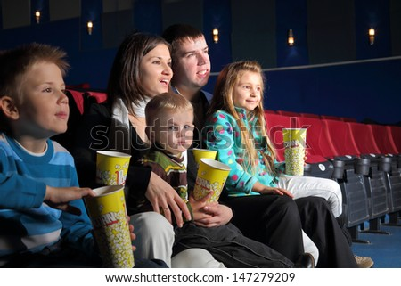 Friendly family watching a movie and eating popcorn in the cinema - stock photo