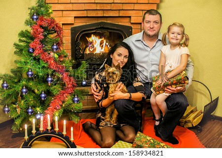 Friendly Family with a Christmas tree and a fireplace - stock photo