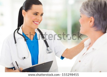 friendly female doctor comforting middle aged patient in hospital - stock photo