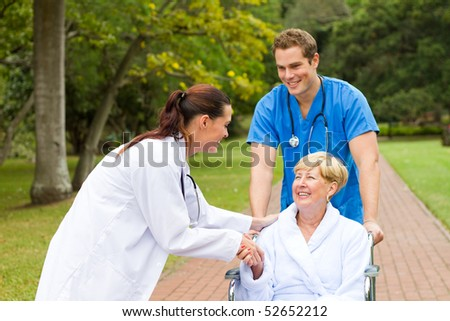 friendly female doctor greeting recovering senior patient in wheelchair outdoors