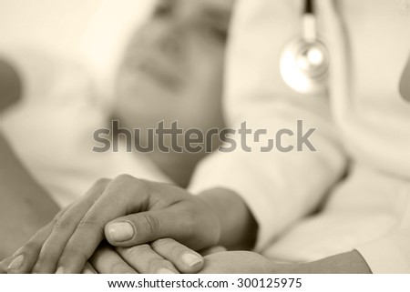 Friendly female doctor hands holding patient hand lying in bed for encouragement, empathy, cheering and support while medical examination. Bad news lessening, compassion, trust and ethics concept - stock photo