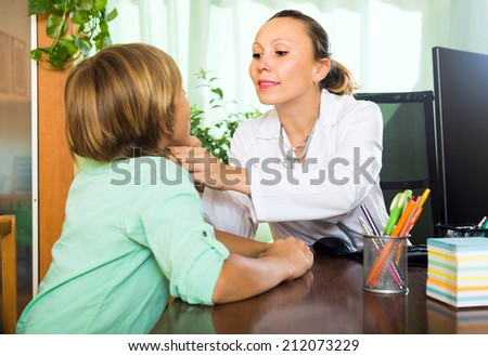 Friendly female doctor in clinic checking thyroid of teenager boy   - stock photo