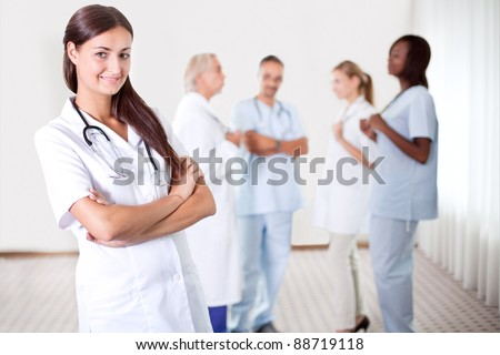 Friendly female doctor with folded hands smiling at the camera with colleagues discussing in the background - stock photo