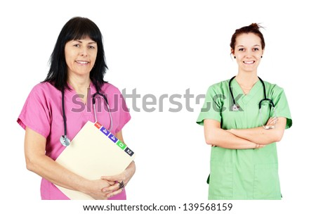 Friendly female doctors or nurses in pink and green scrubs isolated on white. - stock photo