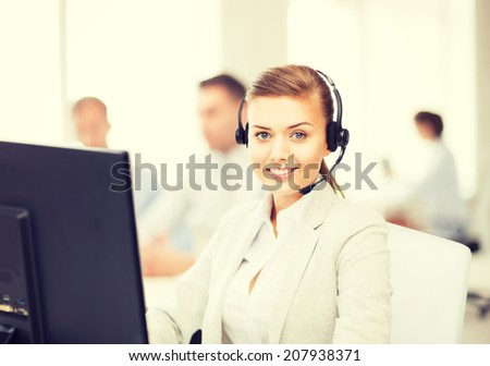 friendly female helpline operator with headphones in call centre - stock photo