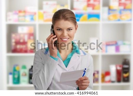 Friendly female pharmacist consulting patient via phone in drug store. Concept of medicine and health. - stock photo