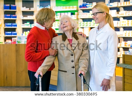 Friendly female pharmacist in pony tail and eyeglasses talking and laughing together in front of pharmacy counter - stock photo