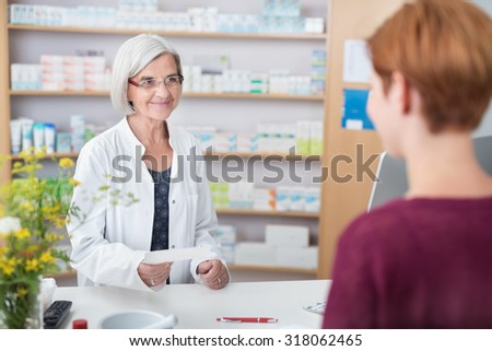 Friendly female pharmacist standing behind her counter at the pharmacy helping a client with a doctors prescription