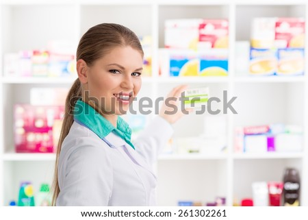 Friendly female pharmacist taking medicine box from the shelf. Young attractive woman medical consultant offering drug to customer.  - stock photo