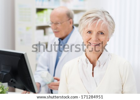 Friendly female pharmacist with a lovely smile greeting the viewer in the pharmacy with a colleague working in the background - stock photo