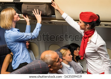 Friendly flight attendant helping passenger to put luggage cabin compartment - stock photo