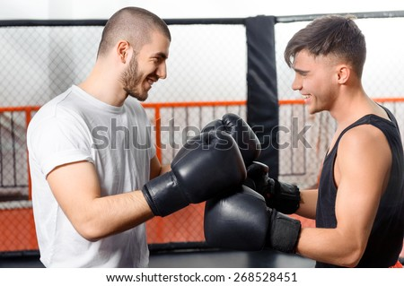Friendly game. Two boxers joyfully laugh standing in a fighting cage - stock photo