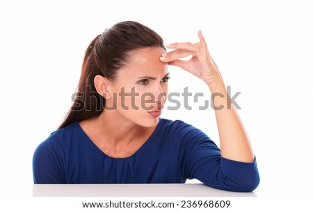 Friendly girl in blue shirt looking embarassed in white background - copyspace - stock photo