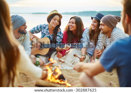 Friendly girls and guys singing by guitar by campfire - stock photo