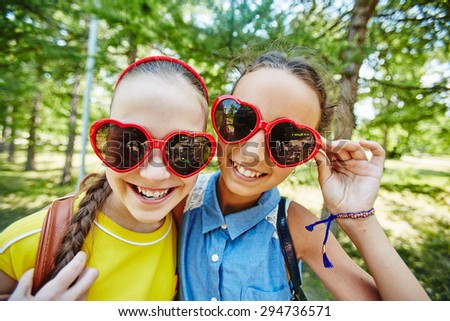 Friendly girls in sunglasses looking at camera outdoors - stock photo