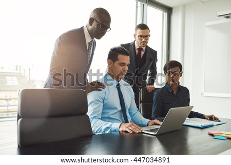 Friendly group of diverse young business people in formal clothing looking at laptop on conference table in front of large window - stock photo