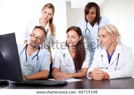 Friendly group of doctors at the hospital looking at a computer