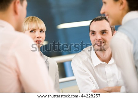 Friendly group of specialists speaking to each other at meeting - stock photo