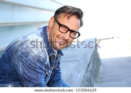 Friendly guy wearing eyeglasses and sitting in town - stock photo