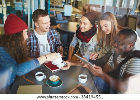 Friendly guys and girls having tea and chatting in cafe - stock photo