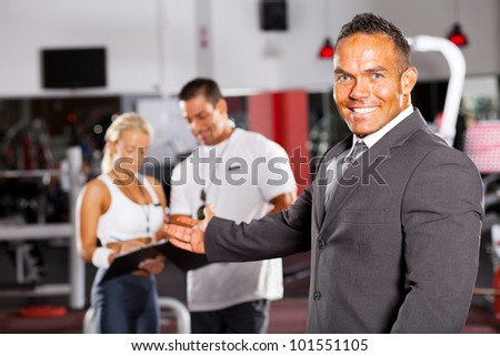 friendly gym manager welcome customer - stock photo