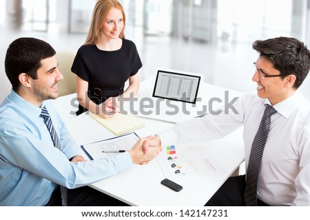 Friendly handshake business people in the office - stock photo