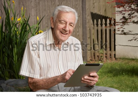 Friendly handsome old man with tablet computer - stock photo